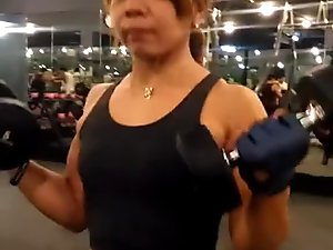 Thai FBB Milf pumping up her biceps 8